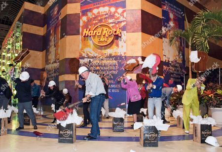 Stock Image of From left; Bloomington Mayor Gene Winstead, President and CEO of Hard Rock International Hamish Dodds, Mall of America owner Tony Ghermezian and musician Morris Day ceremoniously smash guitars to commemorate the Grand Opening of Hard Rock Cafe Mall of America, in Bloomington, Minn