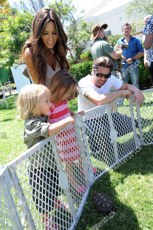 Jillian Barberie, standing, Grant Reynolds, right, and their children attend The HollyRod Foundation's 3rd Annual My Brother Charlie Family Fun Festival at Culver Studios, in Culver City, Calif