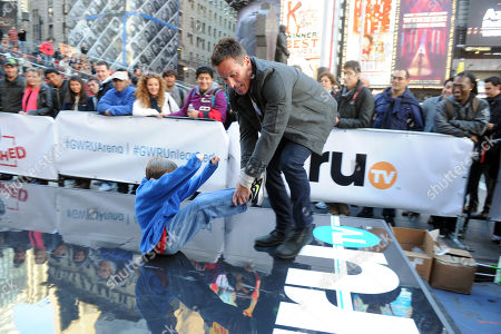 Stock Image of Dan Cortese, right, host of truT's Guinness World Records Unleashed, cheers on a participant of the fastest 20-meter butt scoot at the truTV & GUINNESS WORLD RECORDS event celebrating the premiere of the Guinness World Records Unleashed series, in New York's Times Square