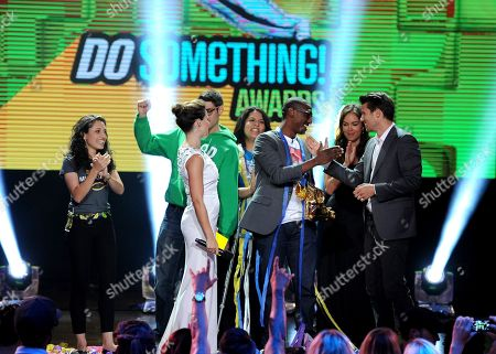 Host Sophia Bush, center left, and winning nominee Daniel Maree of Millionhoodies Movement for Justice, cener right, are seen onstage with presenter Jason Dundas, right, at the 2013 Do Something Awards, on in Hollywood, Calif