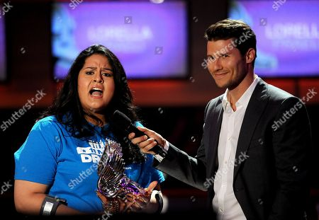 From left, Lorella Praeli of United We DREAM accepts an award from presenter Jason Dundas onstage at the 2013 Do Something Awards, on in Hollywood, Calif