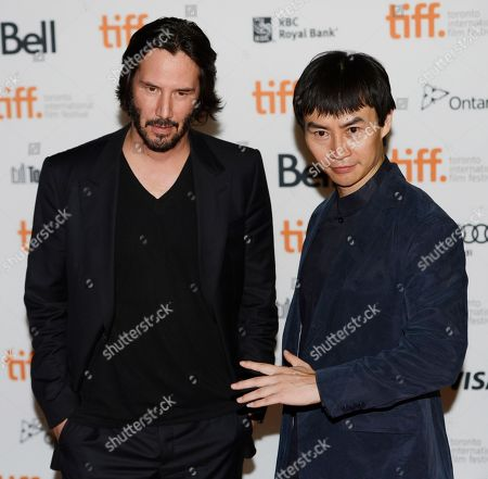 """Stock Picture of Keanu Reeves, left, director and cast member in """"Man of Tai Chi,"""" poses with cast member Tiger Hu Chen at the premiere of the film on day 6 of the 2013 Toronto International Film Festival at the Ryerson Theatre, in Toronto"""