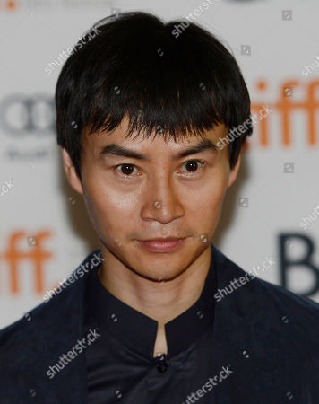 """Tiger Hu Chen, a cast member in """"Man of Tai Chi,"""" poses for photographers at the premiere of the film on day 6 of the 2013 Toronto International Film Festival at the Ryerson Theatre on in Toronto"""