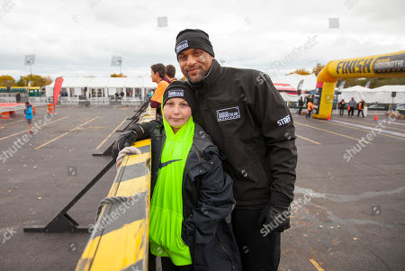 Camren Hagan and celebrity fitness trainer Shaun T at the final obstacle during the 9th annual Men's Health Urbanathlon presented by Polo Red by Ralph Lauren, outside Soldier Field on in Chicago