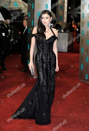 Producer Rebecca Wang arrives at the BAFTA Film Awards wearing a Roberto Cavalli dress and carrying a handbag designed by Judith Leiber at the Royal Opera House in London on