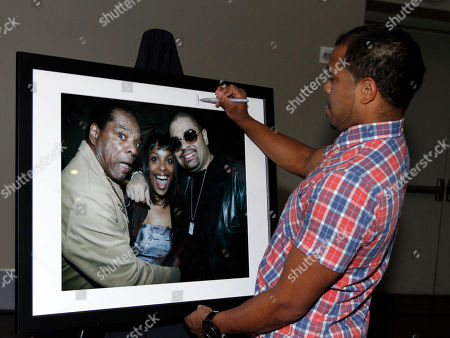 Hip Hop photographer Johnny Nunez signs on of his photos at the BET Music Matters party prior to the BET Hip Hop Awards at the 12th Hotel, in Atlanta, Ga. Several awards nominees, artists and music industry vets were on hand to celebrate the Music Matters initiative to promote emerging new artists