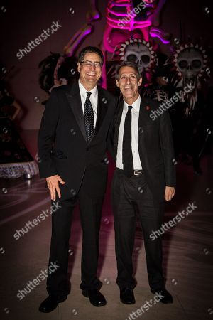 Unidentified guest and CEO of Sony Entertainment Michael Lynton pose for photographers upon arrival at the James Bond Spectre party in London