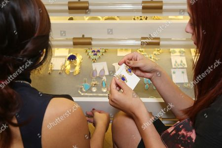 From left, Stacy Ikeda and Emily Centeno look at jewelry during the Luxe Party at the Kendra Scott Fashion Island Boutique, in Newport Beach, Calif