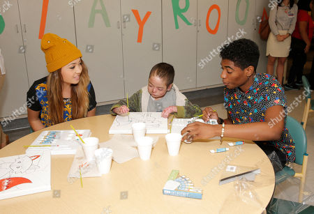 Chloe Jordache and Nadji Jeter paint with a patient at Starlight Children's Foundation's Fun Center dedication at Children's Hospital Los Angeles, in Los Angeles
