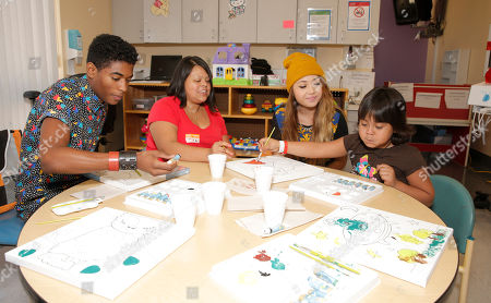 Nadji Jeter and Chloe Jordache (yellow hat) paint with and a patient and her mother attend Starlight Children's Foundation's Fun Center dedication at Children's Hospital Los Angeles, in Los Angeles