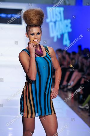 Olympic gold medalist Alex Morgan bites her gold medal while working the runway in a Just Dance 4 inspired look by Tumbler and Tipsy during Fashion Week, in New York