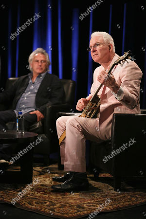From left, artist Eric Fischl watches as Steve Martin plays the banjo during The Un-Private Collection: Eric Fischl and Steve Martin, an art talk presented by The Broad museum and held at The Broad Stage, in Santa Monica, Calif