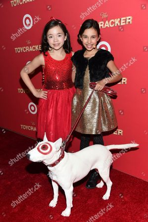 """Actors Isabella Russo, left, and Kylie Cantrall pose with Bullseye the dog at the Target """"Toycracker"""" world premiere at Spring Studios, in New York"""
