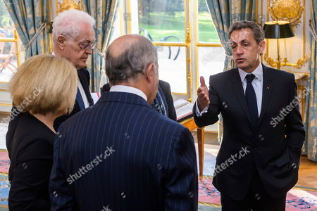 Former French President Nicolas Sarkozy, right, talks to former prime minister Lionel Jospin, Claire Bazy-Malaurie, left,and president of the council and former prime minister Laurent Fabius during newly named member of the Constitutional Council Dominique Lottin's oath-taking ceremony at the Elysee Palace in Paris