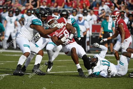 David Williams, Shane Johnson, Nicholas Clark. Arkansas running back running back David Williams is tackled by Costal Carolina defenders Shane Johnson (9) and Nicholas Clark (11) during the first half of an NCAA college football game in Fayetteville, Ark