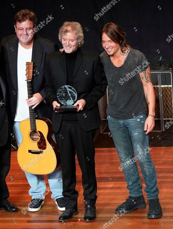 Rodney Crowell, middle, is flanked by artist Vince Gill, left, and Keith Urban, right, after he accepted the The ASCAP Founders Award during the 55th Annual ASCAP Country Music Awards at the Ryman Auditorium, in Nashville, Tenn