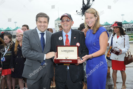 Jennifer Judkins, right, and Juan-Carlos Capelli, left, both of Longines, award owner Kenneth L. Ramsey with his Longines timepiece after his horse Stephanie's Kitten won the Churchill Distaff Turf Mile presented by Longines, in Louisville, Ky., Longines, the Swiss watchmaker known for its famous timepieces, is the Official Watch and Timekeeper of the 139th annual Kentucky Derby