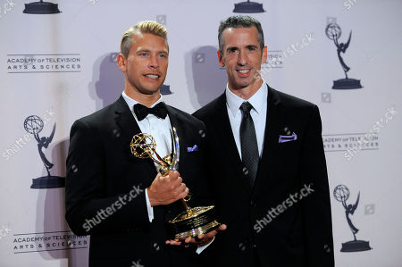 "Dan Savage, right, and Terry Miller pose backstage with the Governors Award for the ""It Gets Better Project"" at the 2012 Creative Arts Emmys at the Nokia Theatre, in Los Angeles"