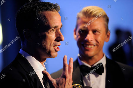 "Dan Savage, left, and Terry Miller pose backstage with the Governors Award for the ""It Gets Better Project"" at the 2012 Creative Arts Emmys at the Nokia Theatre, in Los Angeles"