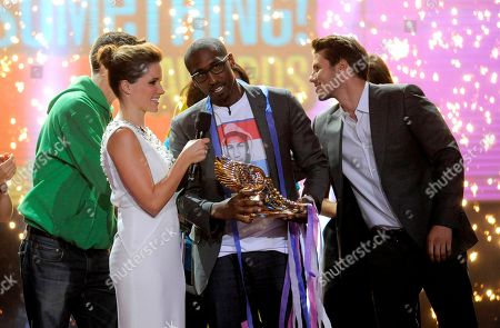 Host Sophia Bush, left, and Jason Dundas, right, present the grand prize to winner Daniel Maree, of Million hoodies Movement for Justice, at the Do Something Awards at the Avalon, in Los Angeles