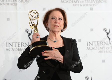 """Stock Picture of Brazilian actress Fernanda Montenegro poses with her """"Best Performance by an Actress"""" award for her role in """"Sweet Mother"""" at the 2013 International Emmy Awards Gala at the New York Hilton on in New York"""