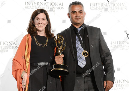 """Algerian producer Christine Camdessus and director Emad Burnat pose with the """"Documentary"""" award for """"5 Broken Cameras"""" at the 2013 International Emmy Awards Gala at the New York Hilton on in New York"""