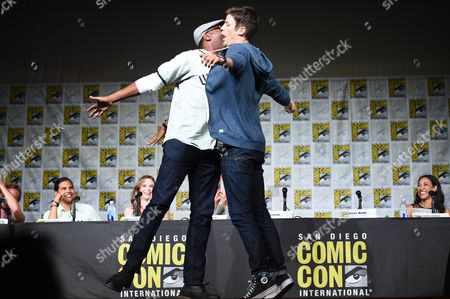"""Jesse L. Martin, left, and Grant Gustin chest-bump as they tap dance on stage at """"The Flash"""" panel on day 3 of Comic-Con International, in San Diego"""