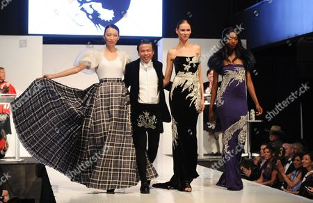 """Stock Picture of Model Ling Tan, left, and fashion designer Zang Toi walk the runway at the """"From Scotland With Love"""" charity fashion show on in New York"""