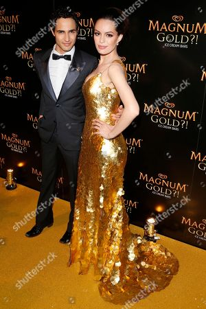 Stock Image of Couture designer Zac Posen, left, and actress Caroline Correa arrive on the gold carpet of the As Good As Gold premiere, a new short film starring Joe Manganiello that celebrates the U.S. arrival of MAGNUM Gold?! Ice Cream. The film debuted during the Tribeca Film Festival in New York. Visit MagnumIceCream.com for more information