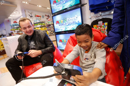 In this photo provided by Nintendo of America, Daniel Cupido, right, of New York, meets celebrity and golf fan Noah Munck during an exclusive media event at Nintendo World, in New York, where they play against one another in Mario Golf: World Tour for Nintendo 2DS and Nintendo 3DS. Mario Golf: World Tour changes the way golf is played with friends. Instead of waiting to take their turns, up to four players can play through courses simultaneously in local wireless or online matches