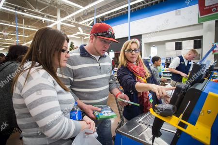 Walmart associate Kathleen Holmes-Smith helps Chris and Mary Finley checkout during Walmart's Black Friday shopping event on in Rogers, Ark. Hundreds of customers at Walmart stores across the country took advantage of deals on top items during the retailer's event