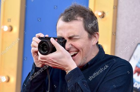 """Director/writer Garth Jennings takes a photograph as he arrives at the world premiere of """"Sing"""" at the Microsoft Theater, in Los Angeles"""