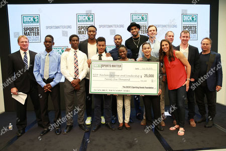 Moderator Jon Gruden and panelists Brandon Marshall, Karl-Anthony Towns, Michael B. Jordan, Carli Lloyd, Buzz Bissinger, and Paul Caccamo pose with a check for the Harlem Lacrosse team at the DICK's Sporting Goods Sports Matter panel at NASDAQ MarketSite on in New York