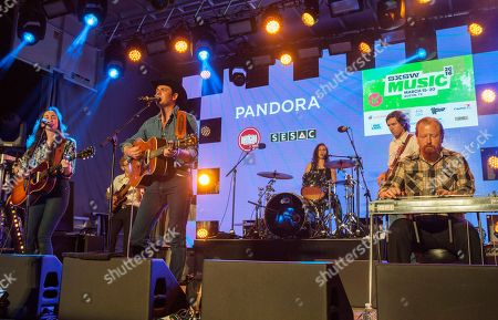 In center, Sam Outlaw and band perform at the Pandora Discovery Den at the SXSW Station, during the South by Southwest Music Festival, in Austin, Texas