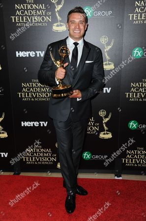 Stock Photo of Billy Miller poses in the press room with the award for outstanding lead actor in a drama series for The Young and the Restless at the 41st annual Daytime Emmy Awards at the Beverly Hilton Hotel, in Beverly Hills, Calif