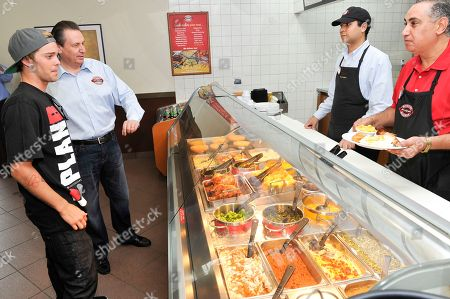 Boston Market CEO George Michel (A.K.A. The Big Chicken) and pro skateboarder Ryan Sheckler order lunch at Boston Market during an event benefiting The Sheckler Foundation on in North Arlington, N.J