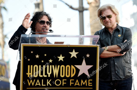 John Oates, left, addresses the audience as his musical partner Daryl Hall looks on during a ceremony to award them a star on the Hollywood Walk of Fame, in Los Angeles