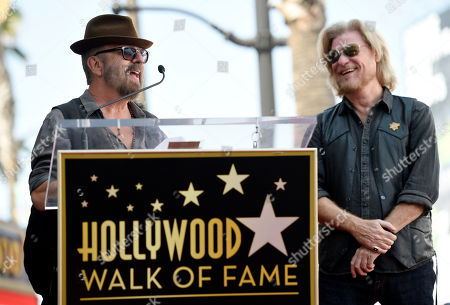 Musician Dave Stewart, left, addresses the crowd as Daryl Hall looks on during a ceremony to award Hall and his musical partner John Oates a star on the Hollywood Walk of Fame, in Los Angeles