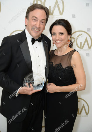 Peter Del Vecho with the award for outstanding producer of an animated theatrical motion picture for Frozen and Julia Louis-Dreyfus backstage at the 25th annual Producers Guild of America (PGA) Awards at the Beverly Hilton Hotel, in Beverly Hills, Calif