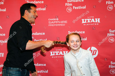 """Actor Jason Isaacs, left, playfully pulls actress Avery Phillips, right, by the pony tail for his turn to pose for photographers at the premiere of """"Stolkholm, Pennsylvania"""" during the 2015 Sundance Film Festival, in Park City, Utah"""