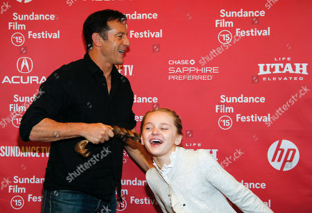 "Actor Jason Isaacs, left, playfully pulls actress Avery Phillips by the pony tail for his turn to pose for photographers at the premiere of ""Stolkholm, Pennsylvania"" during the 2015 Sundance Film Festival, in Park City, Utah"
