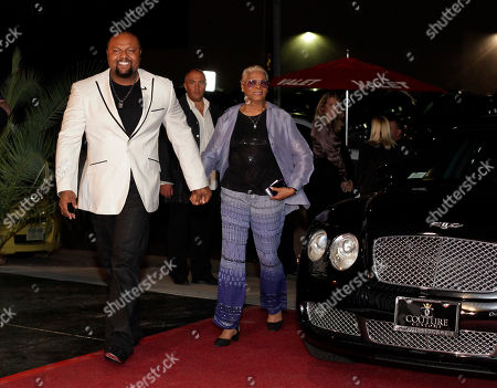 Damon Elliott, left, and Dionne Warwick enter Sy Sahari's Couture Customs at a Celebrity Charity Event on in Scottsdale, Ariz. NFL players announced a Players Authority BFI and DRE Ent Three Day Event to take place during Super Bowl 2015