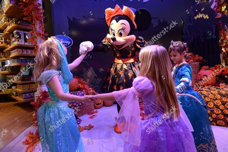 From left, Crystal Burge, Luna Marie and Mia Talerico pose with Minnie Mouse at Disney Store's Halloween BOOtique Party, in Glendale, CA