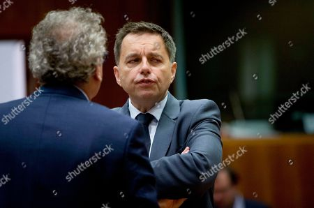Slovakian Finance Minister Peter Kazimir, right, speaks with Luxembourg's Finance Minister Pierre Gramegna during a meeting of EU finance ministers at the EU Council building in Brussels on