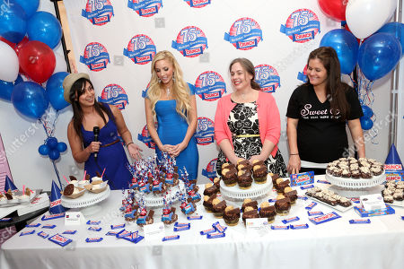 Stock Photo of From left, Nastassia Johnson, director of operations, Coolhaus, Casey Reinhardt, owner of Casey's Cupcakes, Lisa Hess-Marks, head baker at Crumbs bakery and Erica Tucker, owner of Sweet E's participate in the kick-off of the Nestle Crunch 75th Birthday Showdown at Sweet E's on in Los Angeles. Fans can vote at Facebook.com/NestleCrunch for their favorite treat or bakery in the Nestle Crunch 75th Birthday Showdown