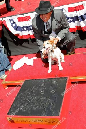 Owner, trainer Omar Von Muller and superstar Dog Uggie attend the pawprint ceremony for Uggie the dog at Grauman's Chinese Theatre on in Los Angeles