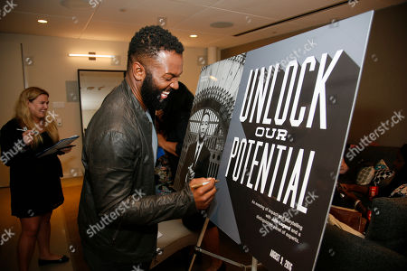 Moderator Baratunde Thurston signs a poster as he participates in the Television Academy's UNLOCK OUR POTENTIAL member event at the Academy's Wolf Theater and Saban Media center on in Los Angeles