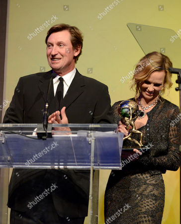 Wayne Gretzky, left, and Janet Jones accept the Alfred Mann Foundation award for innovation and inspiration at the 10th annual Alfred Mann Foundation Gala, in Beverly Hills, Calif