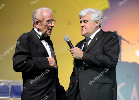 Alfred Mann, left, and Jay Leno speak on stage at the 10th annual Alfred Mann Foundation Gala, in Beverly Hills, Calif