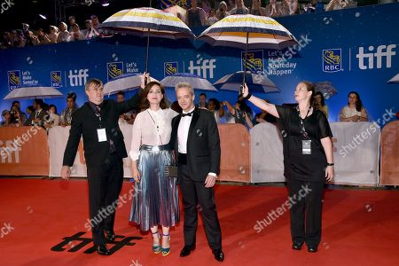 "Rebecca Zlotowski, left, and Emmanuel Salinger arrive at the ""Planetarium"" premiere while event staff hold umbrellas to protect from the rain on day 3 of the Toronto International Film Festival at Roy Thomson Hall, in Toronto"
